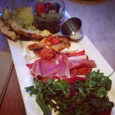 Antipasto Platter | Marinated olives, fior-di-latte with eggplant caponata, sliced italian meats, arugula salad, and flatbread.